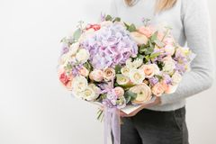 Lilac and light bouquet of beautiful flowers in women`s hands. Floristry concept. Spring colors. the work of the florist Stock Photo