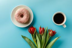 A bouquet of beautiful fresh tulips on a blue background and cakes with a cup of coffee royalty free stock photos
