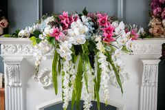 Bouquet of beautiful mixed flowers in vase on the fireplace. Lovely bunch of flowers. Work of the professional florist. Wedding or stock images