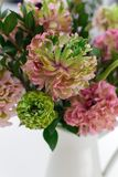Bouquet of beautiful pink and green ranunculus flowers. And myrtle in minimal interior stock photo