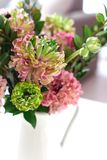 Bouquet of beautiful pink and green ranunculus flowers. And myrtle in minimal interior royalty free stock image