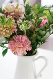 Bouquet of beautiful pink and green ranunculus flowers. And myrtle in minimal interior royalty free stock photography
