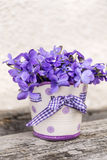 Bouquet of beautiful purple violets flowers in a small vase Stock Image
