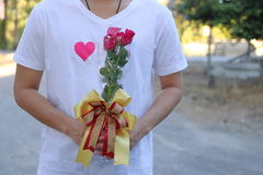 A Bouquet of beautiful red roses is held by young handsome man in white shirt. Valentine`s day or dating concept.  Stock Image