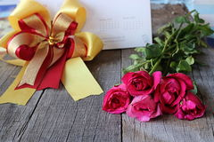 Bouquet of beautiful red roses with ribbon on old wooden background. Valenday`s day or wedding concept Royalty Free Stock Image