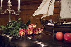 Bouquet of beautiful roses, model sailboat and two apples on a b Royalty Free Stock Image