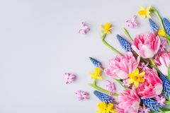 Bouquet of beautiful spring flowers on pastel table top view. Greeting card for International Women Day. Flat lay. Style stock photos