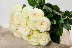 Bouquet of beautiful tea-roses on a banquette Royalty Free Stock Photos