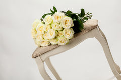 Bouquet of beautiful tea-roses on a banquette Stock Photos
