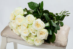 Bouquet of beautiful tea-roses on a banquette Stock Photography