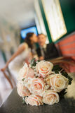 Bouquet from beige roses and a kiss of the groom and the bride on a background Stock Photography