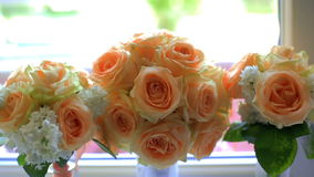 Bouquet of beige roses in vases on the windowsill. Wedding day stock video