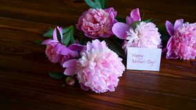 Bouquet of blooming peonies. On a wooden table