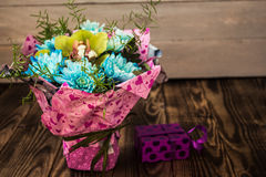 Bouquet of blue daisies and orchid with gift box stock photos