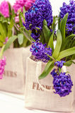Bouquet of blue hyacinth in canvas bag. Bouquet of blue hyacinth  in beige canvas bag with written word: flowers Stock Photo