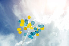 Bouquet of blue and yellow balloons in the sky Stock Images