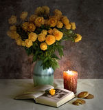 The bouquet, the  book and cookies. The bouquet, the opened book and cookies in a view of a candle Stock Photo
