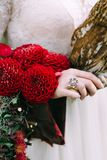 Bouquet with bordeaux dahlias on bride hand. Vintage ring. Wedding decoration. Royalty Free Stock Photo