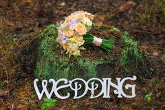 Bouquet of bridal wedding flowers. On top of old stump. Decorated place in old autumn wood for wedding ceremony. Rustic style of elements of decor. White wooden Royalty Free Stock Image