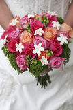 Bouquet and bride. High angle view of young woman dressed in wedding dress wearing holding bouquet of roses, mid-section Royalty Free Stock Photography