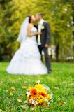 A bouquet for the bride on the background of kissing pair. A bouquet for the bride on the background of the kissing pair Stock Photos
