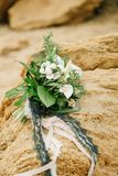Bouquet of a bride from feces and roses lies on a sandstone. Stone on the seashore Stock Photos