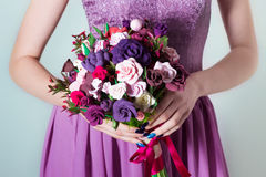 Bouquet for the bride, girl in purple evening dress holding a large bouquet of multicolored roses in hand Royalty Free Stock Photo