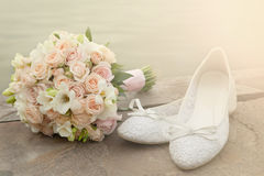 Bouquet and bride shoes closeup. Bridal bouquet and shoes lie on the bank of the pond, in the light of the sun. Bouquet and white orchids and roses closeup Royalty Free Stock Photography
