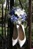 Bouquet and shoes of the bride. Bouquet and bride shoes on a metal fence Stock Images