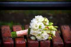 Bouquet of a bride on a white bench. Beautiful wedding bouquet.  Royalty Free Stock Image