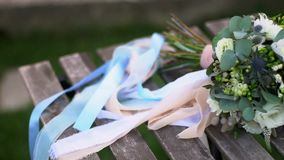 Bouquet of the bride with white roses. Lies on a wooden bench stock video