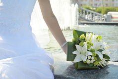 Bouquet in brides hand sitting at fountain Royalty Free Stock Photos