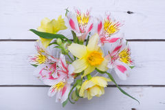 A bouquet of bright colors: a daffodil and alstroemeria in a vas. E on a wooden table. Spring bouquet on a white background, top view Stock Images
