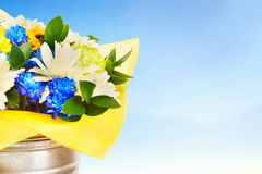 Bouquet of bright flowers in a metal bucket against blue sky Stock Images