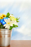 Bouquet of bright flowers in a metal bucket on wooden surface Stock Image