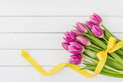 Bouquet of bright pink tulips decorated with yellow ribbon on white wooden background Royalty Free Stock Photos