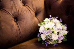 Bouquet in brown sofa - Purple and creamy roses royalty free stock image