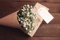 Bouquet of camomile. Field wrapped in kraft paper on a wooden table Stock Image