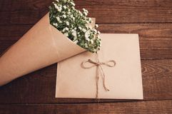 Bouquet of camomile. Field wrapped in kraft paper on a wooden table Royalty Free Stock Images