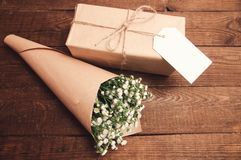 Bouquet of camomile. Field wrapped in kraft paper on a wooden table Stock Photo