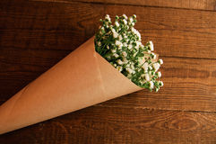 Bouquet of camomile. Field wrapped in kraft paper on a wooden table Royalty Free Stock Image