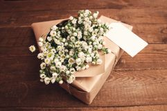 Bouquet of camomile. Field wrapped in kraft paper on a wooden table Royalty Free Stock Photo