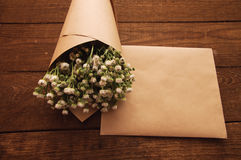 Bouquet of camomile. Field wrapped in kraft paper on a wooden table Royalty Free Stock Photos