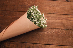 Bouquet of chamomile. Bouquet of camomile field wrapped in kraft paper on a wooden table Royalty Free Stock Image