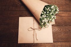 Bouquet of chamomiles. Bouquet of camomile field wrapped in kraft paper on a wooden table Stock Photography