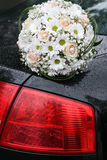 Bouquet on a car. Bouquet of daisies and roses on a car Royalty Free Stock Image