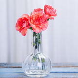 Bouquet of Carnations in glass vase. Orange carnations om wooden table indoors stock images