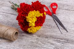 A bouquet of carnations tied with a rope on a wooden background stock images