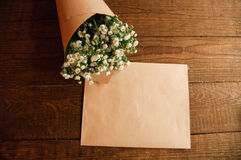 Bouquet of chamomile. Bouquet of camomile field wrapped in kraft paper on a wooden table Royalty Free Stock Photo