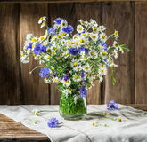 Bouquet of chamomiles and cornflowers in the vase. Bouquet of chamomiles and cornflowers in the vase on the wooden table royalty free stock images